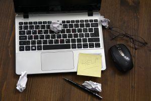 Laptop mit zerknitterten Papier und einem Post-IT HELP